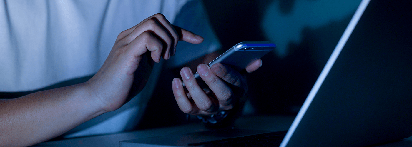 Person using smartphone and laptop in a dark room