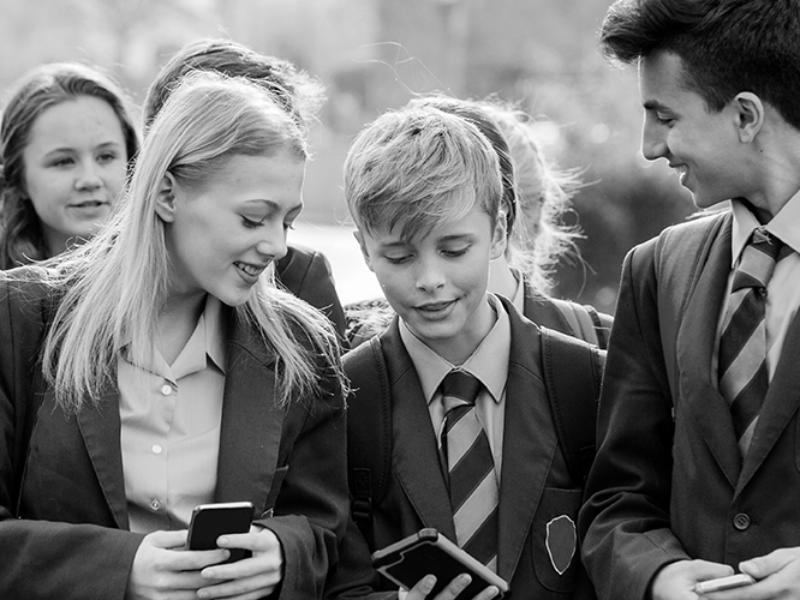school children on mobiles