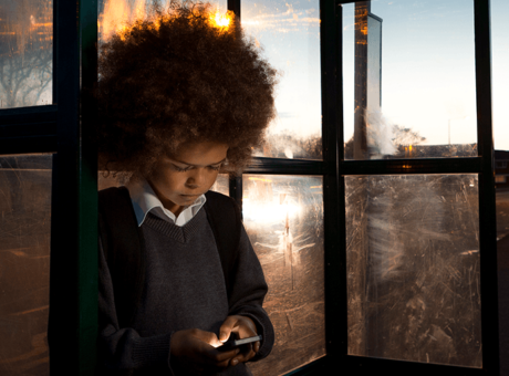 School boy looking sad on mobile phone at the bus stop